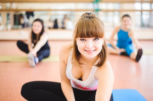Grupa ludzi na siłowni w klasie rozciągania.