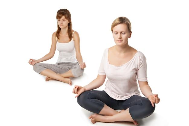 Grupa ludzi odpoczywających i uprawiających jogę w bieli?