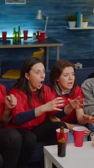 Grupa ludzi oglądających mecz piłki nożnej w telewizji dopingujących drużynę sportową po wygraniu mistrzostw