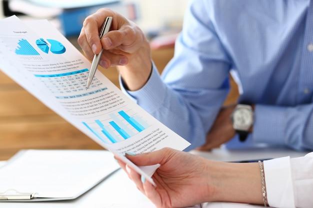 Grupa ludzi omawia wyniki finansowe w miejscu pracy