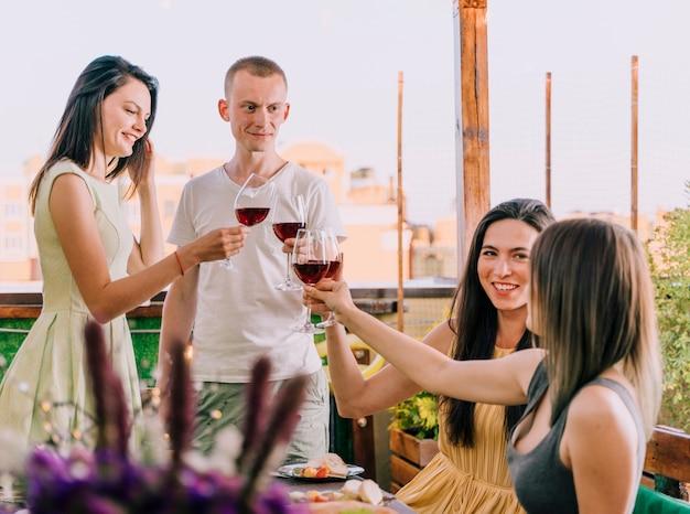 Grupa ludzi opiekania na imprezie na dachu
