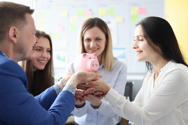 Grupa ludzi posiadających różową skarbonkę w biurze