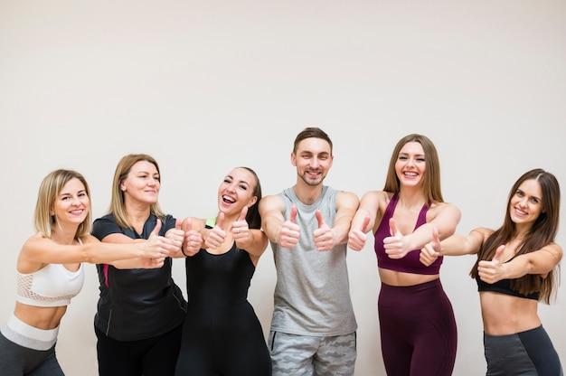 Grupa ludzi pozuje wpólnie przy gym
