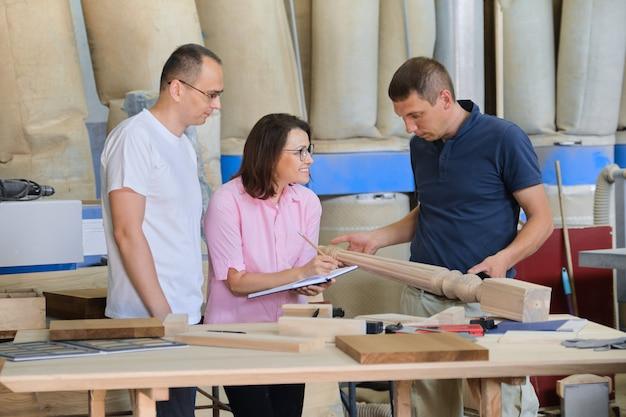 Grupa ludzi pracy omawiająca przebieg pracy, wyroby z drewna w warsztacie stolarskim