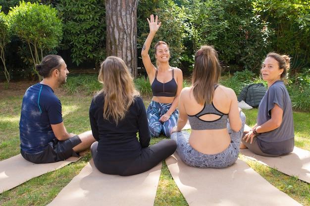 Grupa ludzi przychodzących razem na zewnątrz jogi