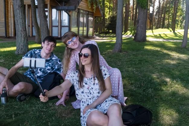 Grupa ludzi robi sobie selfie na trawniku w parku, trzech uśmiechniętych przyjaciół, patrząc w aparat w smartfonie