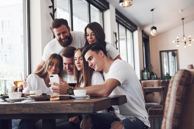 Grupa ludzi robi zdjęcie selfie w kawiarni. najlepsi przyjaciele zebrali się przy stole, jedząc pizzę i śpiewając różne napoje