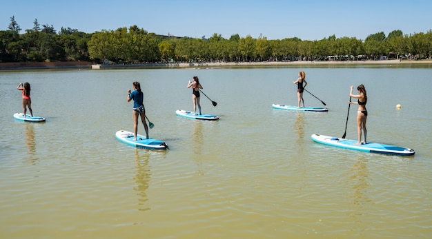 Grupa ludzi robiących wiosło surfing