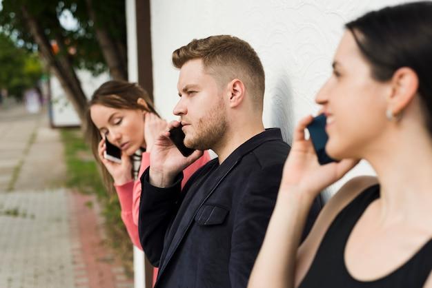 Grupa ludzi rozmawia przez telefony na zewnątrz