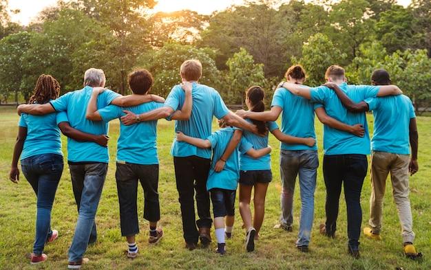 Grupa ludzi różnorodności wolontariuszy uzbraja się w ramię