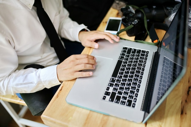 Grupa ludzi różnych narodowości zadowolony i wesoły na sukces pracują z laptopem w nowoczesnym biurze.