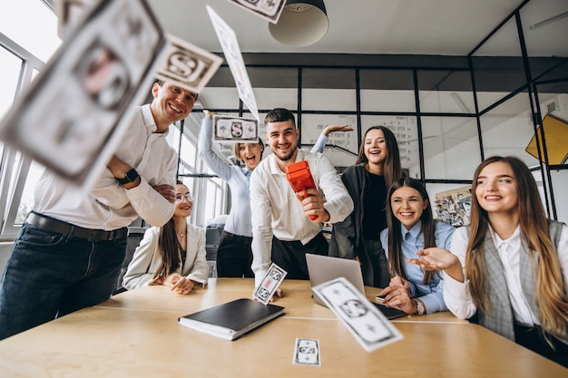 Grupa ludzi rzuca pieniądze w biurze
