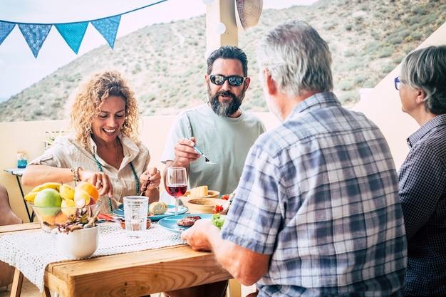 Grupa ludzi siedzących w domu z dużym stołem pełnym jedzenia i napojów - koncepcja rodziny na świeżym powietrzu na tarasie - córka, grzech, babcia i dziadek baw się razem i jedząc