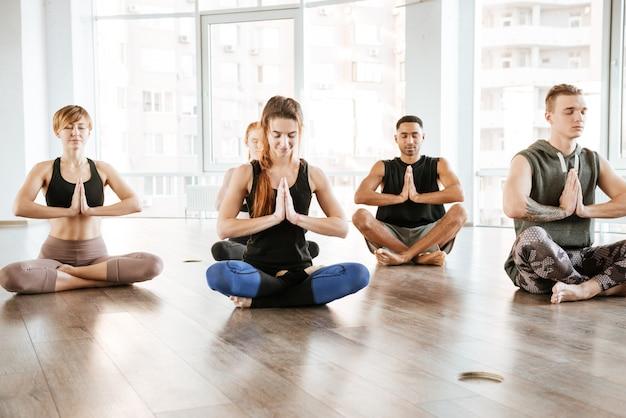 Grupa ludzi siedzi i medytuje w studio jogi