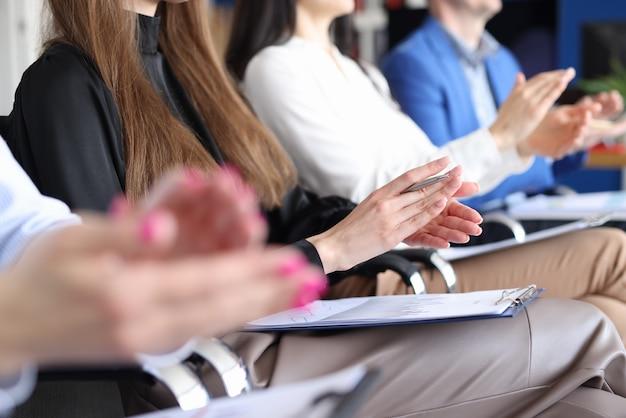 Grupa ludzi siedzi na biznesowym kursie edukacyjnym i klaszcząc w ręce zbliżenie