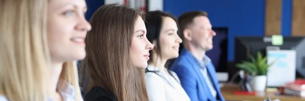 Grupa ludzi siedzi na fotelu z dokumentami w rękach i słucha wykładu