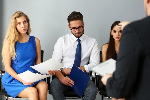 Grupa ludzi siedzi na rzędzie krzesła casting w recepcji szefa