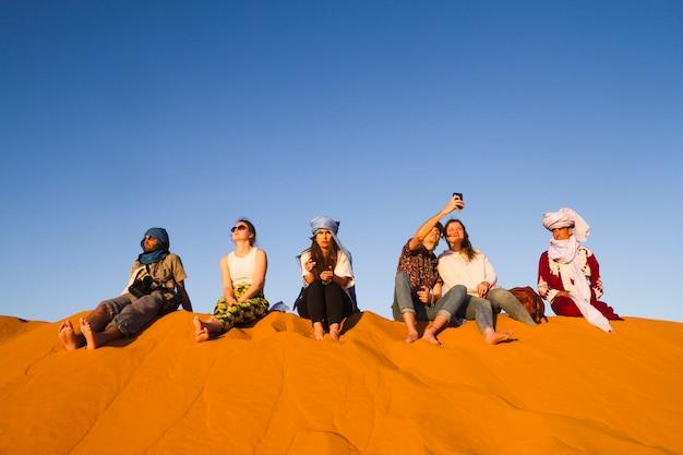 Grupa ludzi siedzi na szczycie wydmy