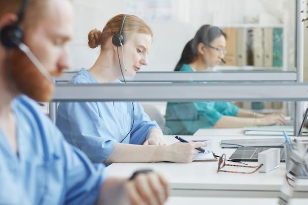 Grupa ludzi siedzi przy stole i rozmawia z klientami w medycznym centrum telefonicznym