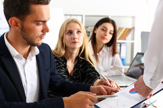 Grupa ludzi siedzi w biurze, rozmyślając nad problemem
