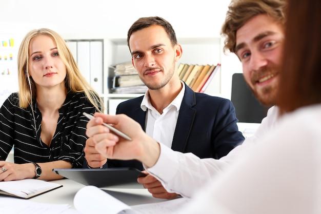Grupa ludzi siedzi w biurze, rozważając portret problemu.