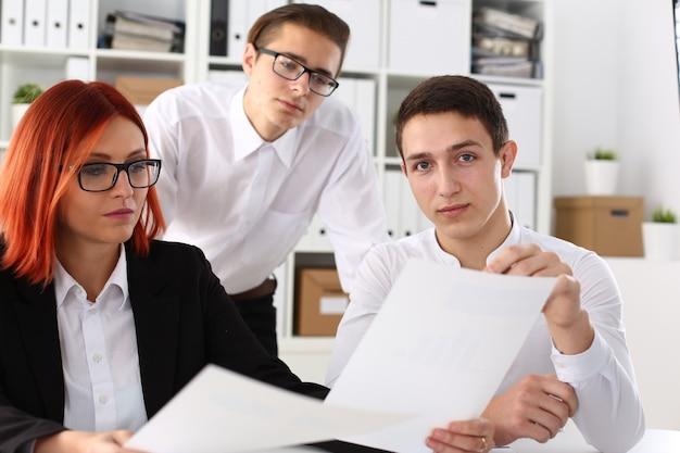 Grupa ludzi siedzi w biurze, rozważając portret problemu