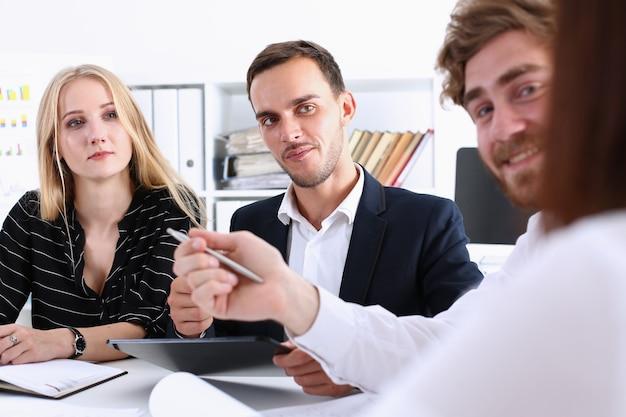 Grupa ludzi siedzi w biurze, rozważając problem