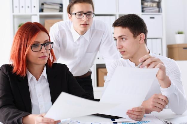Grupa ludzi siedzi w biurze, zastanawiając się nad problemem