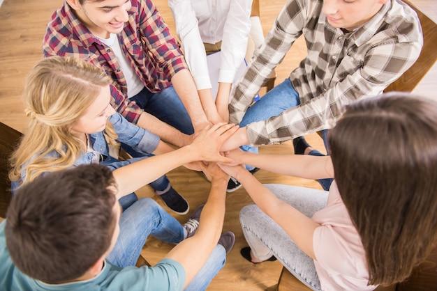 Grupa ludzi siedzi w kręgu i wspierają się nawzajem.