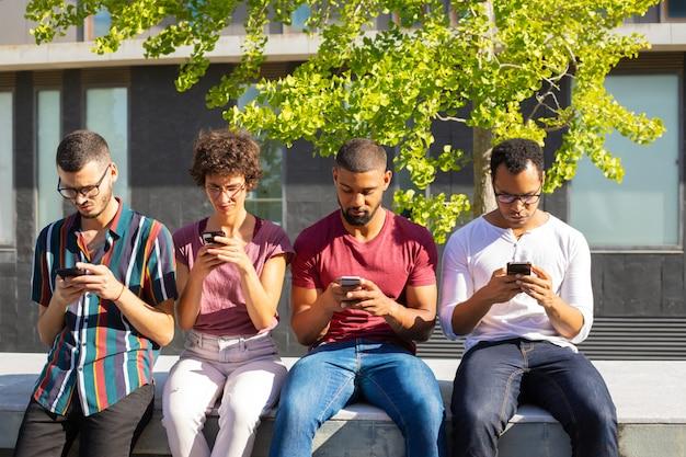 Grupa ludzi skupiła się na swoich smartfonach