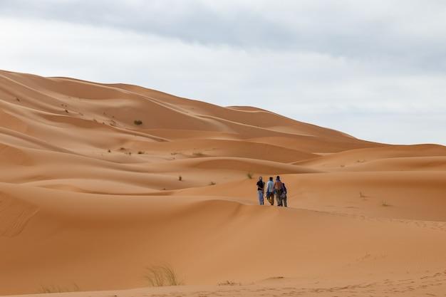 Grupa ludzi spaceruje po wydmach na saharze w maroku