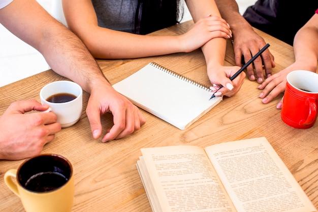 Grupa ludzi studiuje wraz z kawą na drewnianym biurku