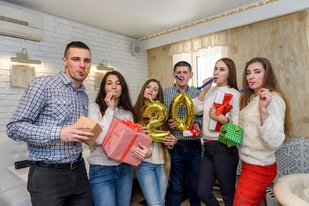 Grupa ludzi świętujących z balonami i pudełkami na prezenty