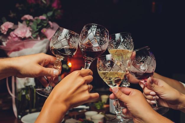 Grupa ludzi szczęk kieliszków z winem i szampanem