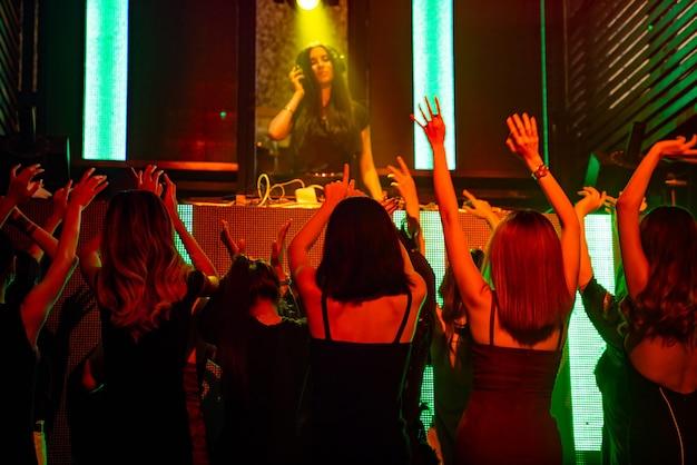 Grupa ludzi tańczy w dyskotece w rytm muzyki dj-a na scenie