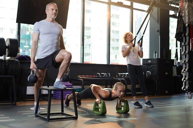 Grupa ludzi trenujących z hantlami i sprzętem sportowym w siłowni