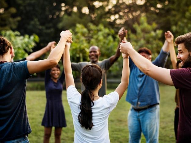 Grupa ludzi trzyma rękę w parku wpólnie