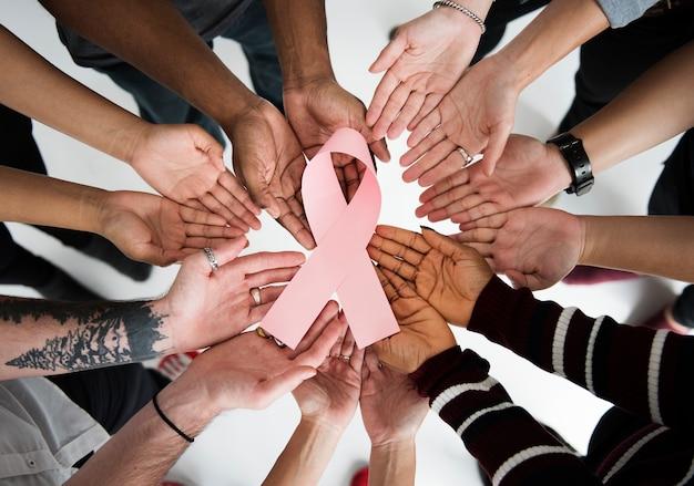 Grupa ludzi trzyma tasiemkowego nowotworu piersi pojęcie