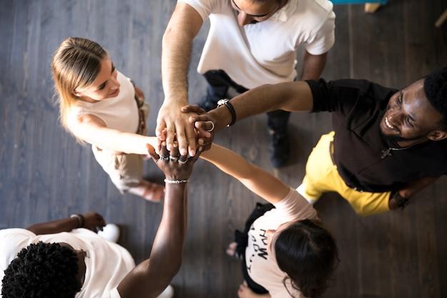 Grupa ludzi, trzymając ręce w górę