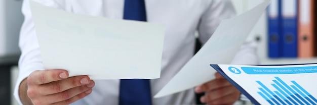 Grupa ludzi trzymających w ręku dokumenty finansowe rozwiązuje i dyskutuje problem