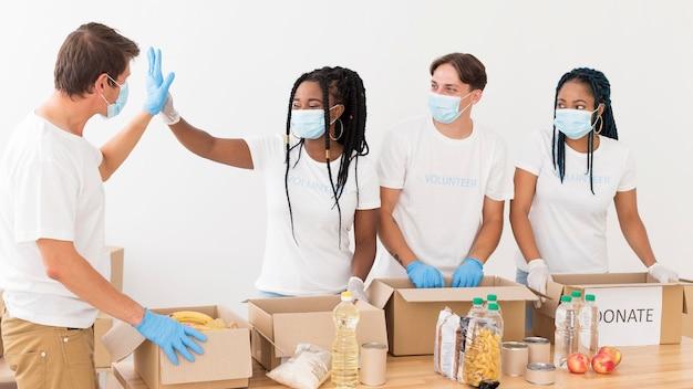 Grupa ludzi tworzących zgrany zespół podczas wolontariatu