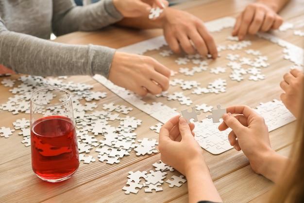 Grupa ludzi układających puzzle na drewnianym stole