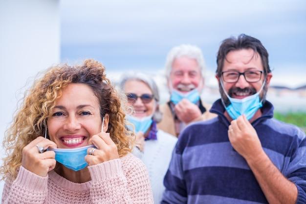 Grupa ludzi uśmiechających się i patrzących w kamerę zdejmującą maskę medyczną i chirurgiczną po koncepcji koronawirusa i kwarantanny - pandemiczny styl życia covid 19 w masce