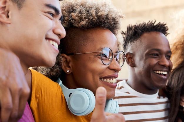 Grupa ludzi, uśmiechnięci i szczęśliwi, że są razem. latynoska przytulająca się z przyjaciółmi, afroamerykaninem i azjatą. pojęcie studentów wieloetnicznych.