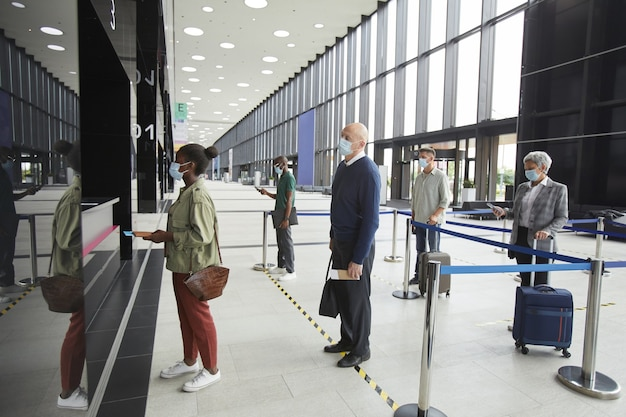Grupa ludzi w maskach ochronnych osoby zachowujące dystans społeczny na lotnisku stojąc w kolejce