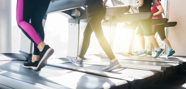 Grupa ludzi w odzieży sportowej biegających na bieżni. trening cardio na siłowni.