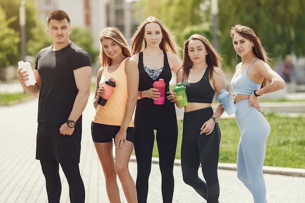 Grupa ludzi w parku. chłopiec z czterema dziewczynami. sportowcy z butelkami wody.