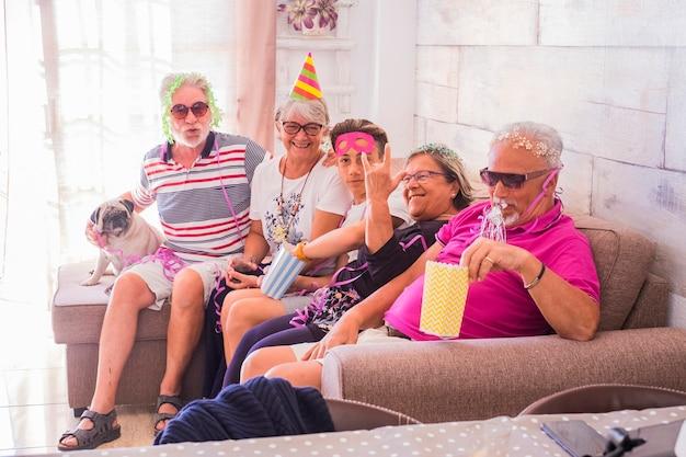 Grupa ludzi w różnym wieku, od dziadków do nastolatka, bawiących się razem podczas obchodów urodzin - koncepcja rodziny w domu z karnawałowymi farszami i maskami - różnorodność ludzi styl życia z senio