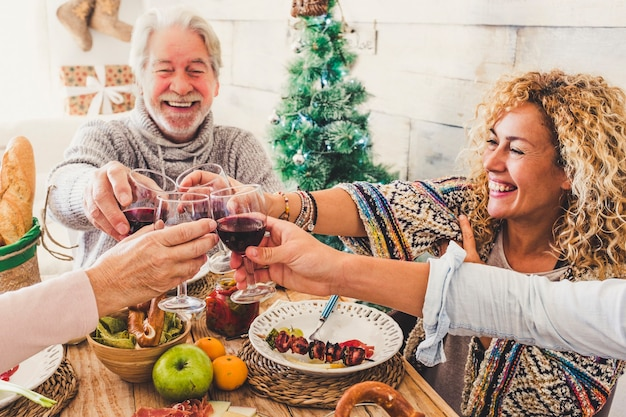 Grupa ludzi w różnym wieku, takich jak przyjaciele lub wesoła rodzina rasy kaukaskiej, bawi się razem w domu podczas świąt bożego narodzenia, brzęcząc i wznosząc toast czerwonym winem