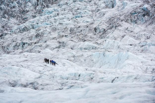 Grupa ludzi wędruje po lodowcu